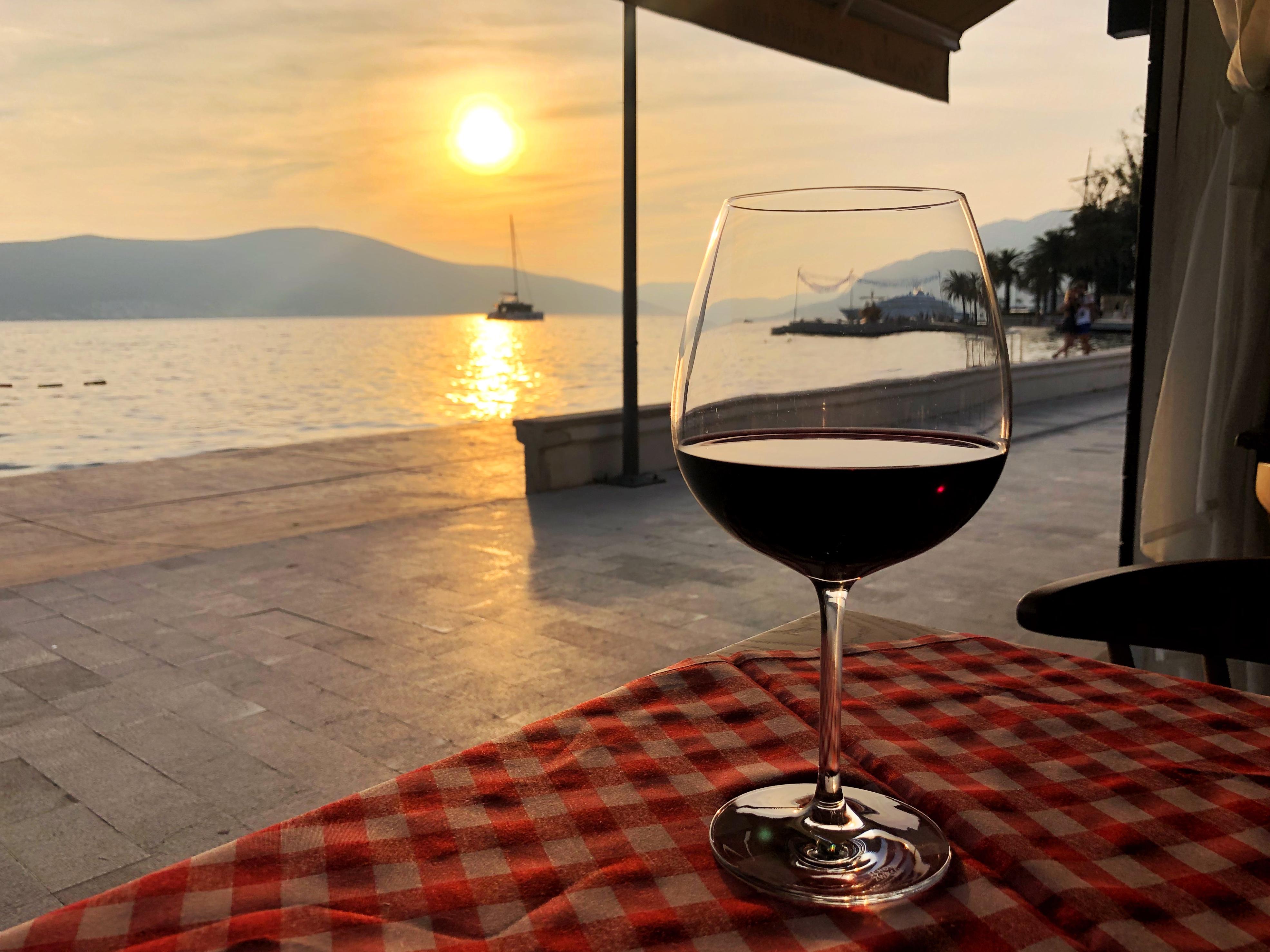 Čaša vina na stolu, sa pogledom na zalazak sunca u restoranu Bevanda Tivat