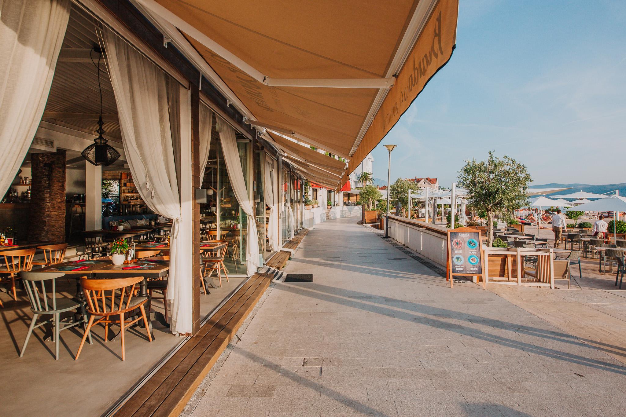 Fotografija restorana Bevanda Tivat, spolja sa pogledom na terasu pored mora.